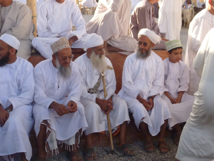 Maenner in traditionelle Kleidung beim Tiermarkt in Nizwa