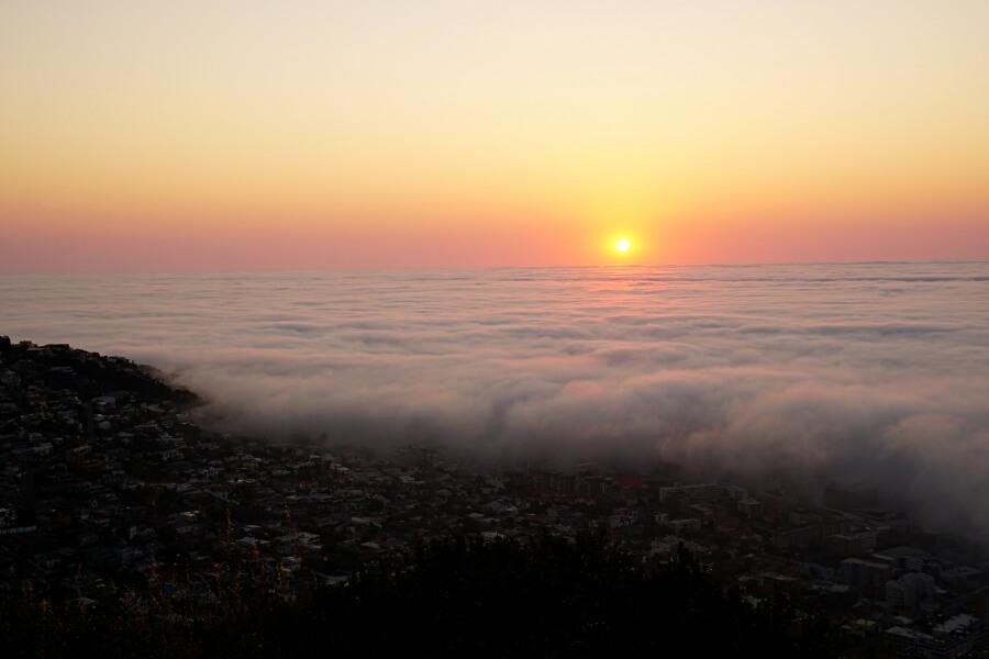 Die Sonne versinkt in einem aufziehenden Meer an Wolken am Signal Hill in Kapstadt
