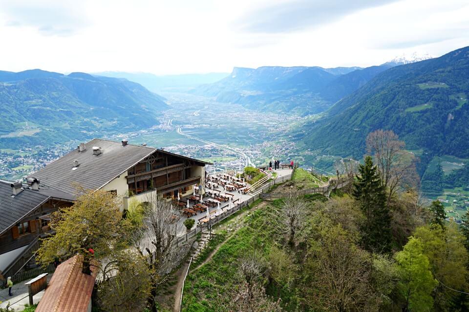 Ausblick ueber den Berggasthof Hochmuth und das Meraner Land vom Meraner Hoehenweg
