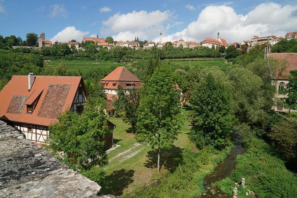 Blick vom Taubertal mit der Doppelbruecke nach Rothenburg ob der Tauber beim Wandern um Rothenburg